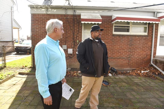 Real Estate One agent Russ Ravary, left, shows a house for sale in Redford Township to Jerome DuBose of Detroit on April 26.  A tight housing market in recent years has driven up single-family prices by more than 70% since 2012 statewide.