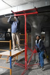 Fitz and Reed Mechanical employees Melvina Thompson, right, operates a hoist to move duct work for her brother, David Thompson, at the development project at 2937 East Grand Boulevard in Detroit.