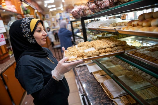 Employee Mervat Charara pulls out a tray of mamoul, a pistachio pastry that is popular during Ramadan.