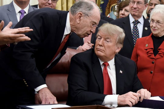 Senate Finance Chairman Chuck Grassley, left, talks to President Trump during a signing ceremony last December in the Oval Office.