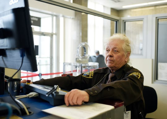 April Hutchings, 75, views a monitor at the entrance to Oakland County Court in Pontiac. She retired from full-time work at the Oakland County Sheriff's Office in 2010 and has been working part-time for the department  for 9 years.