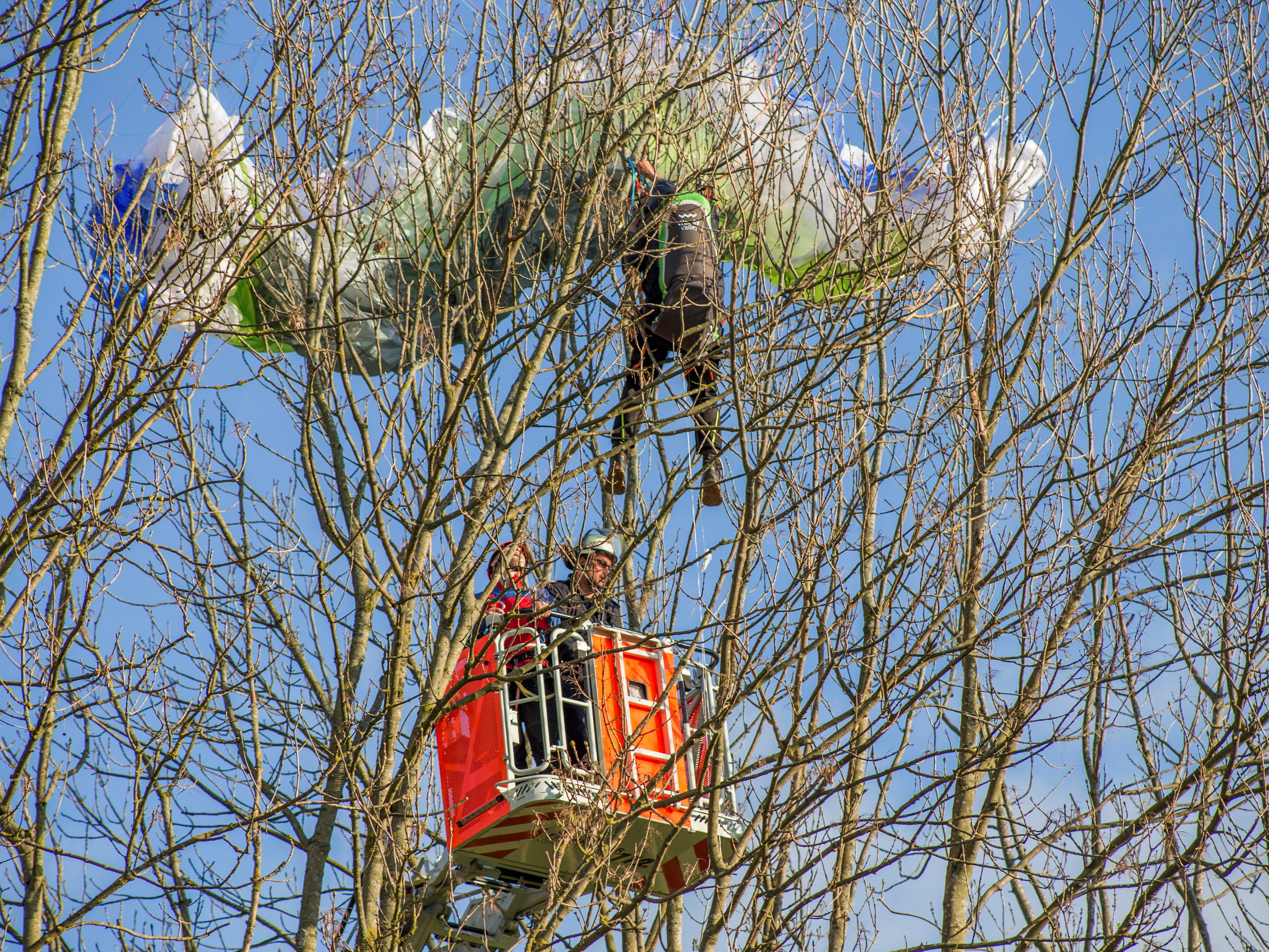 A paraglider is rescued from a tree by fire men in Poppenhausen, central Germany, Monday, April 29,2019.