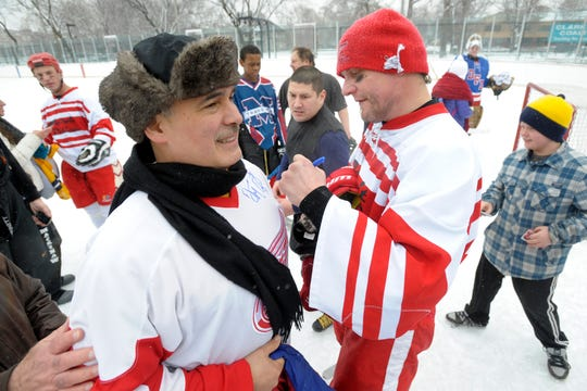 Anthony Benavides, left, gets his jersey signed by Darren McCarty during a charity game at Clark Park in 2012.