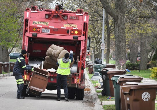 A trash collection crew works on Hampton Road in Grosse Pointe Woods, Monday. Contractor Green for Life, the city said, now must travel further to empty its trucks, delaying their progress.