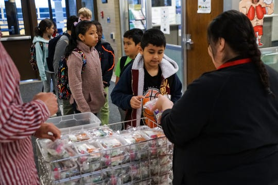 Cafeteria manager Dawn Medina, right passes out breakfast packets to students entering the Fairfield Elementary School in Fort Wayne on April 26, 2019, as part of the Community Eligibility Provision (CEP) program which reimburses eligible public and private school systems and schools for serving meals free of charge to all students.