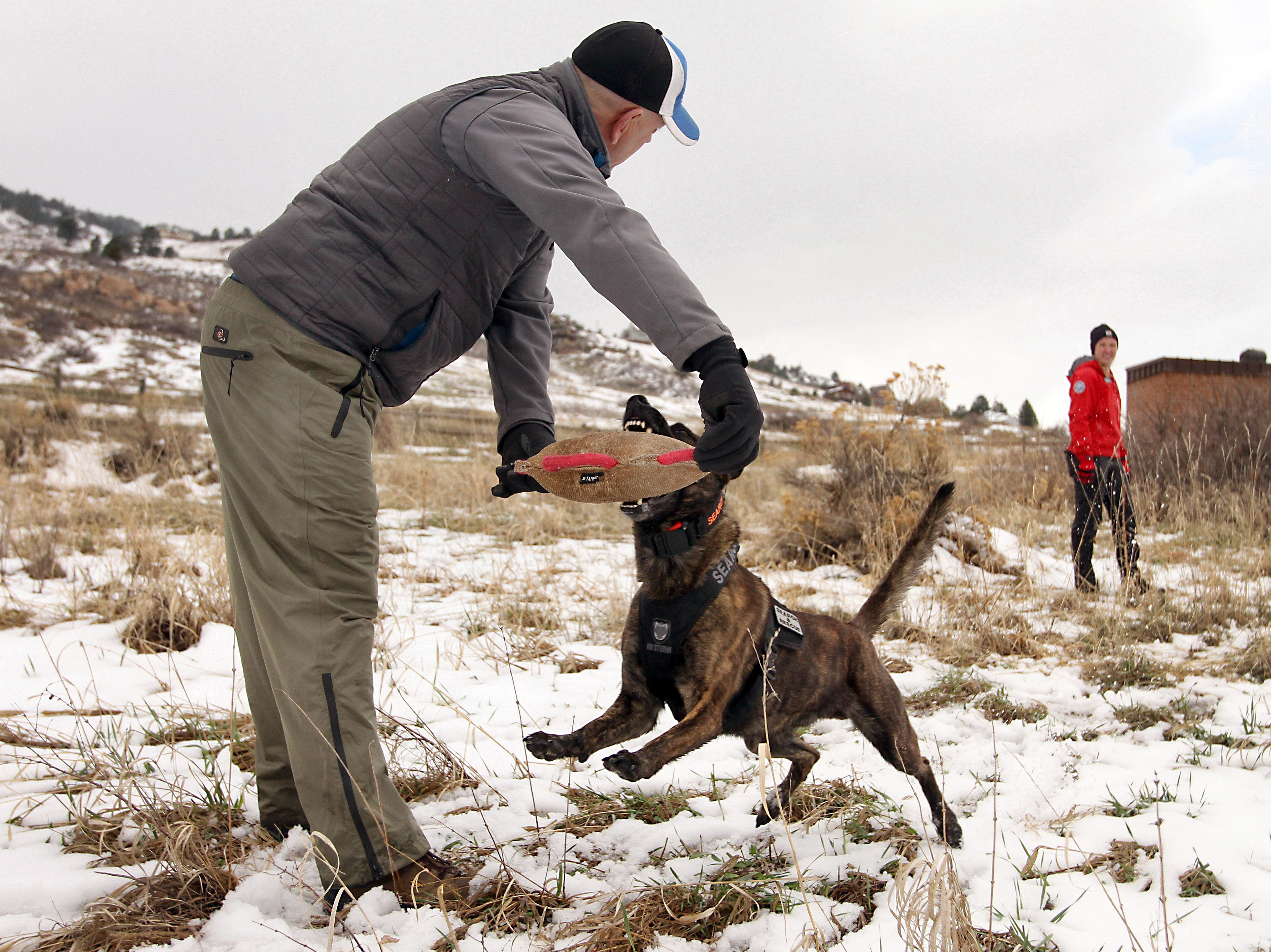 Jay Rigdon, foreground, a member of the Montrose County Sheriffs office and West Elk Mountain Rescue team, holds a tug-upon as a reward for Jupiter, a Larimer County Search and Rescue team member who works with Mary Babbitt, far right, during a training event held at Lory State Park on Saturday, April 13, 2019.
