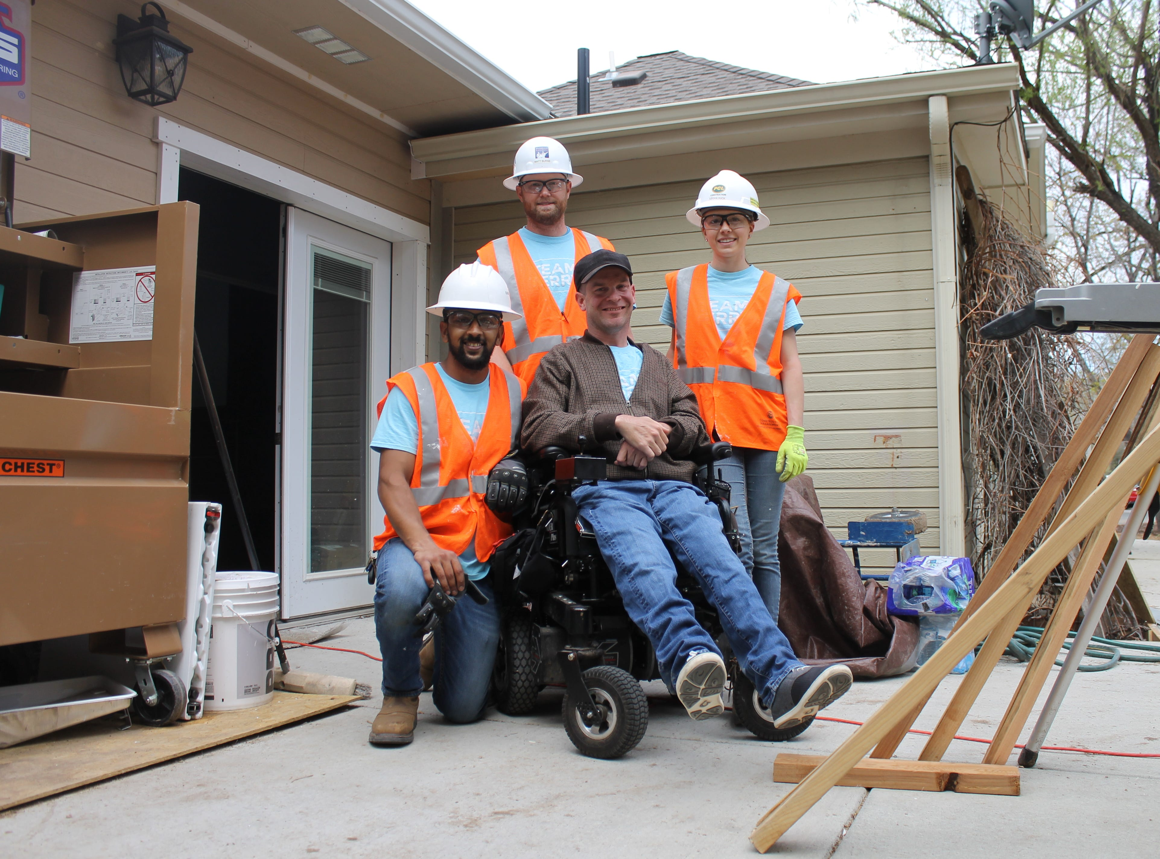 Colorado State University students Saleh Bawareth, Matt Burns and Leigha Huck pose for a photo with homeowner Terry Schlicting. A group of students with CSU's Construction Management Cares program have been working on Schlicting's house since February, making improvements to the bathroom, the patio and more.