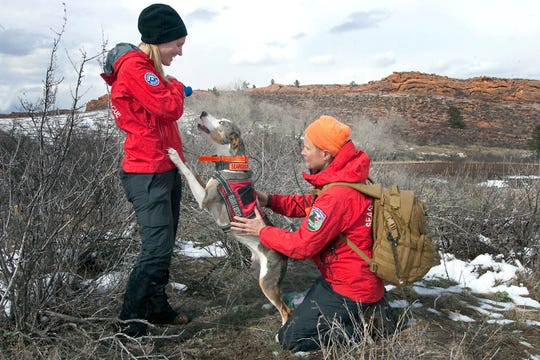 Joel Blocker / For the ColoradoanLarimer County Search and Rescue team members, from left, Mary Babbitt and Chris Robertson, reward RobertsonÕs dog, Bohannon, an air scent dog, after he found his target during a training event held at Lory State Park on Saturday, April 13, 2019. Air cent dogs are trained to detect scent particles that are carried through the wind from a missing person's location.