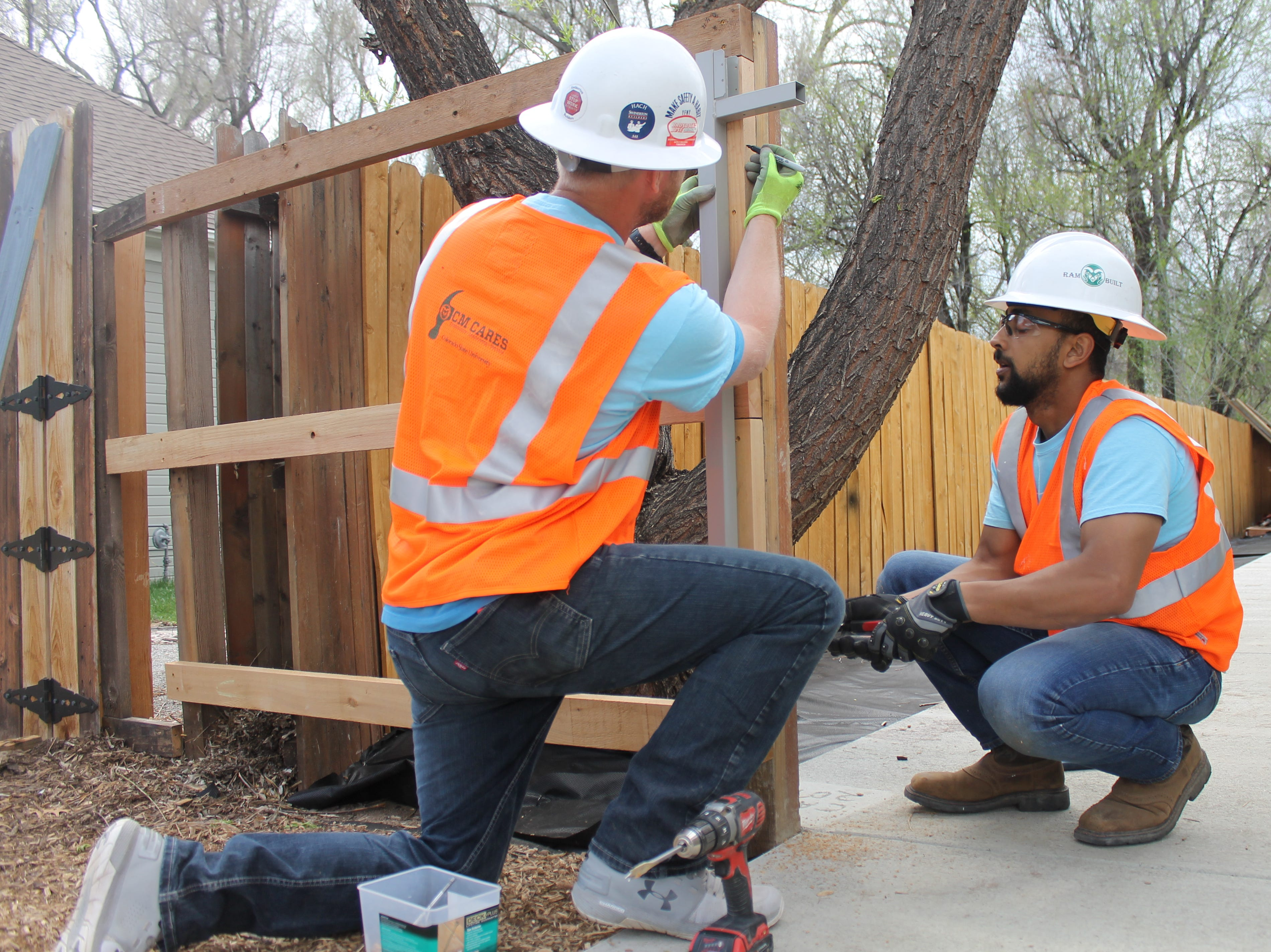 Matt Burns, left, and Saleh Bawareth work to build a gate on Saturday, April 27, 2019 that homeowner Terry Schlicting can easily use in his wheelchair. The students began working on the house in February as part of a class project.