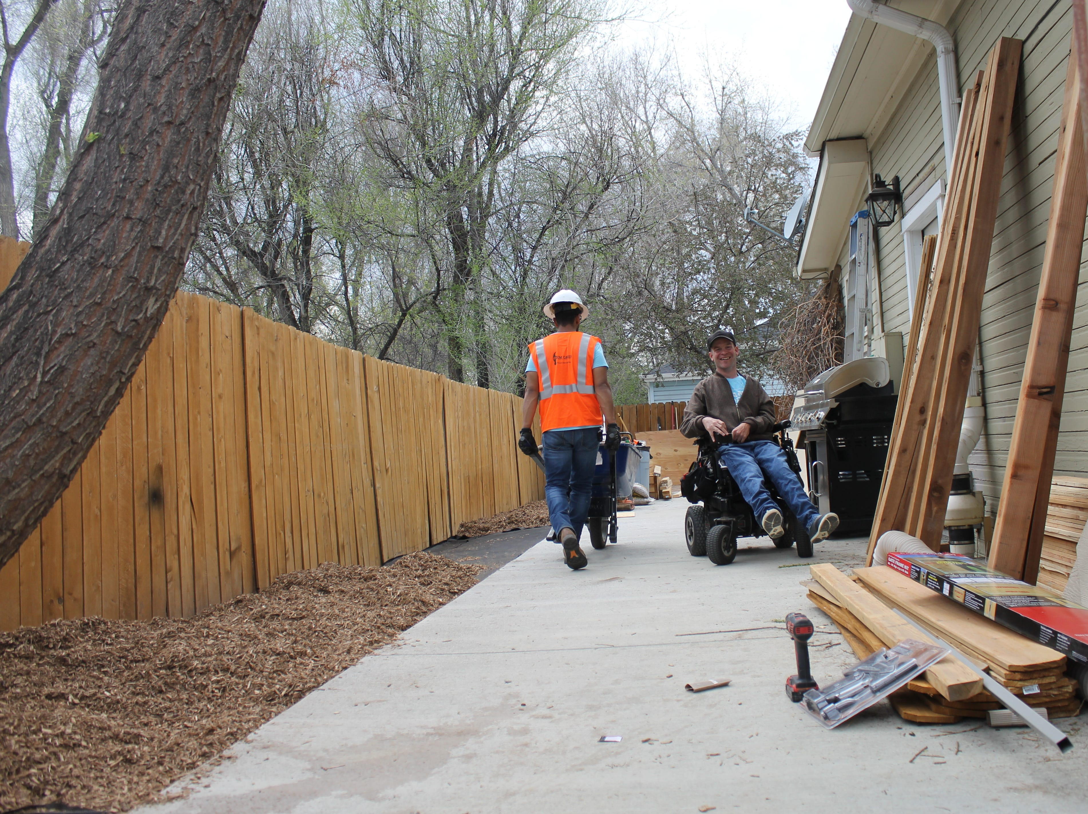 Colorado State University student Saleh Bawareth, left, and property owner Terry Schlicting exchange a laugh as Bawareth hauls mulch Saturday, April 27, 2019. A team of students has been working to make improvements to Schlicting's house since February. Their aim is to make Schlicting's home more wheelchair accessible.