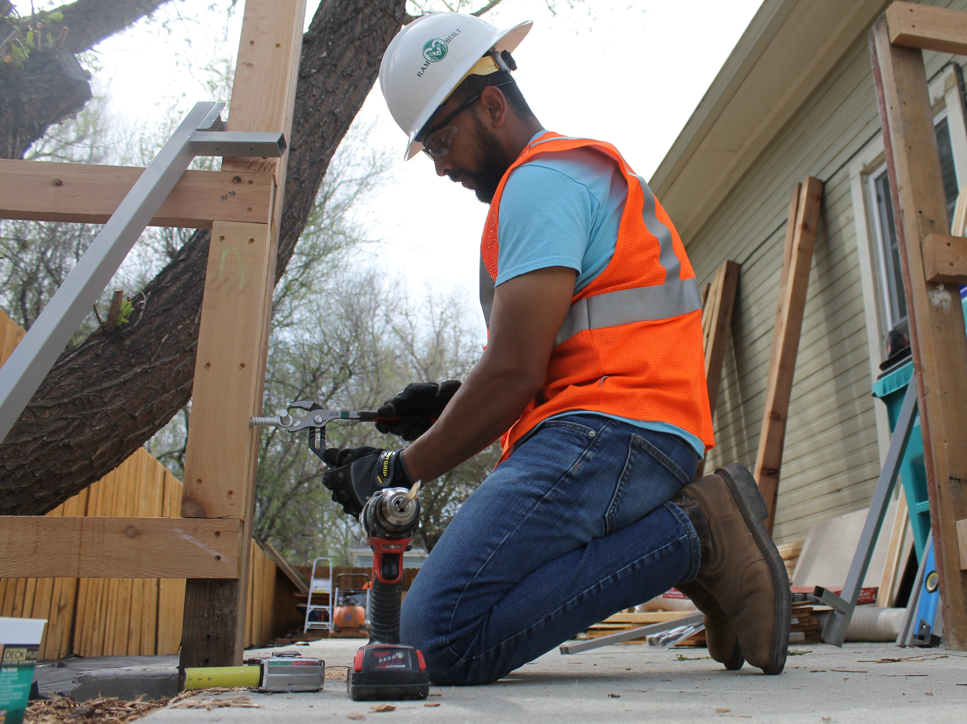 Saleh Bawareth, a construction management student at Colorado State University, works to craft a gate that homeowner Terry Schlicting can easily use in his wheelchair.
