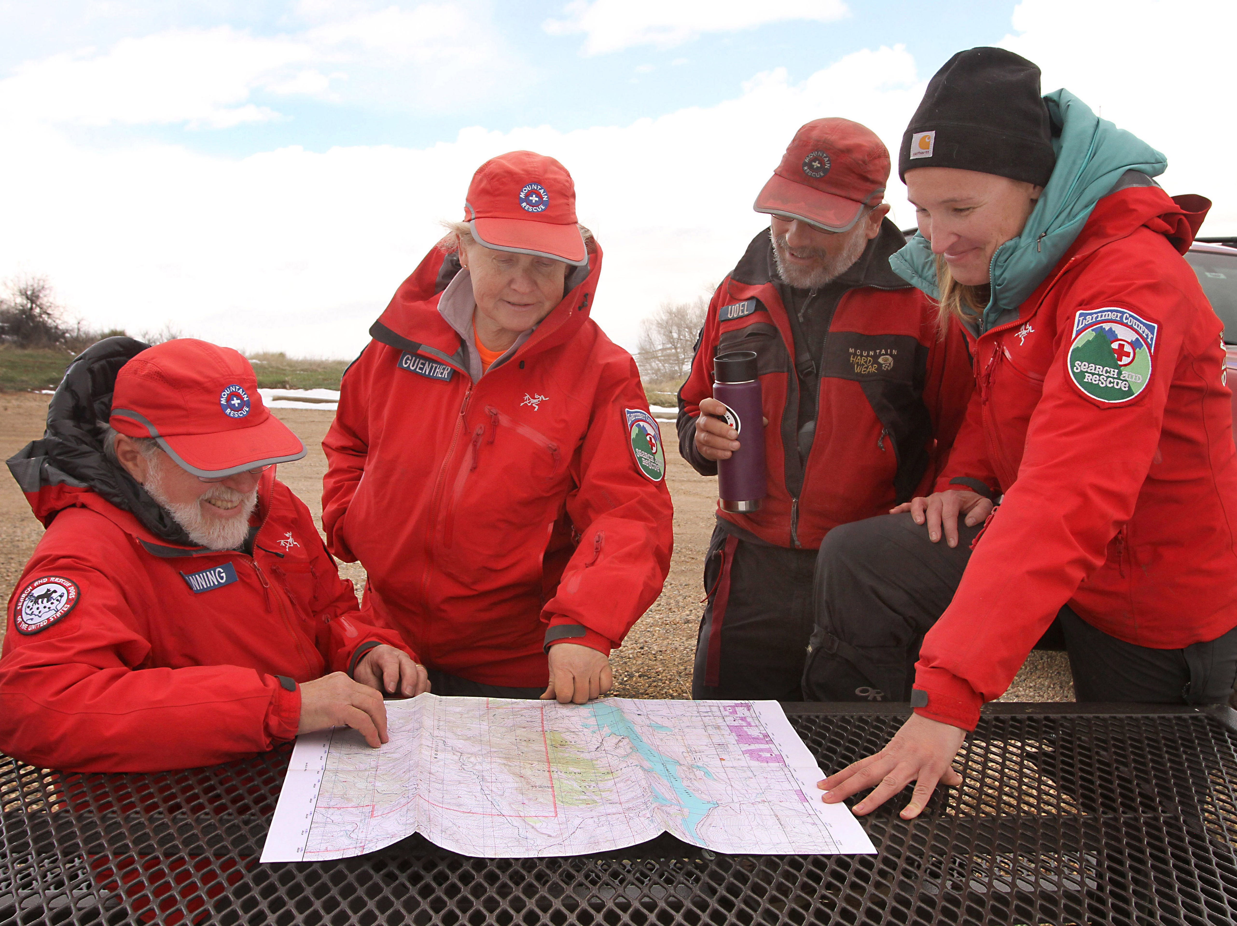 Larimer County Search and Rescue team members, from left, Dan Fanning, Ronnie Guenther, Jake Udel and Mary Babbitt scour an area map looking for locations to train their search and rescue dogs during a training event held at Lory State Park on Saturday, April 13, 2019.