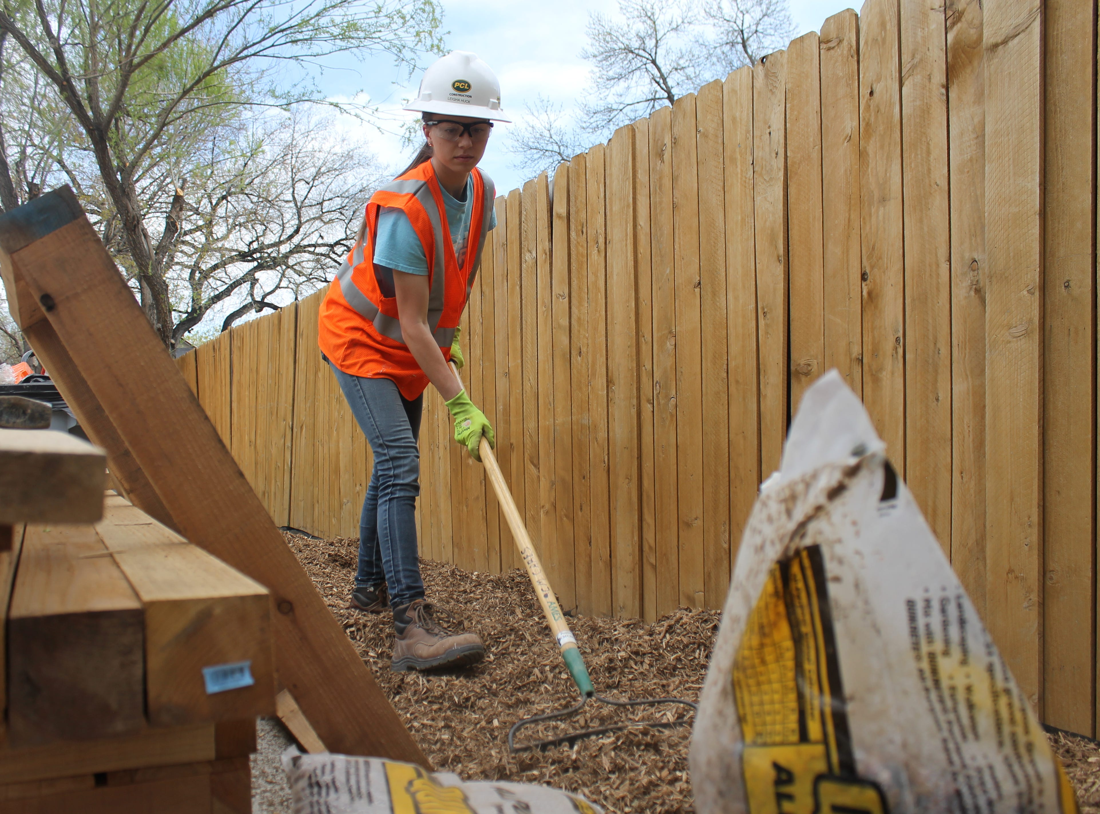 Colorado State University construction management student Leigha Huck works to set down mulch Saturday, April 27, 2019. Huck is part of the Construction Management Cares program, working to make home improvements for folks in the community with disabilities.
