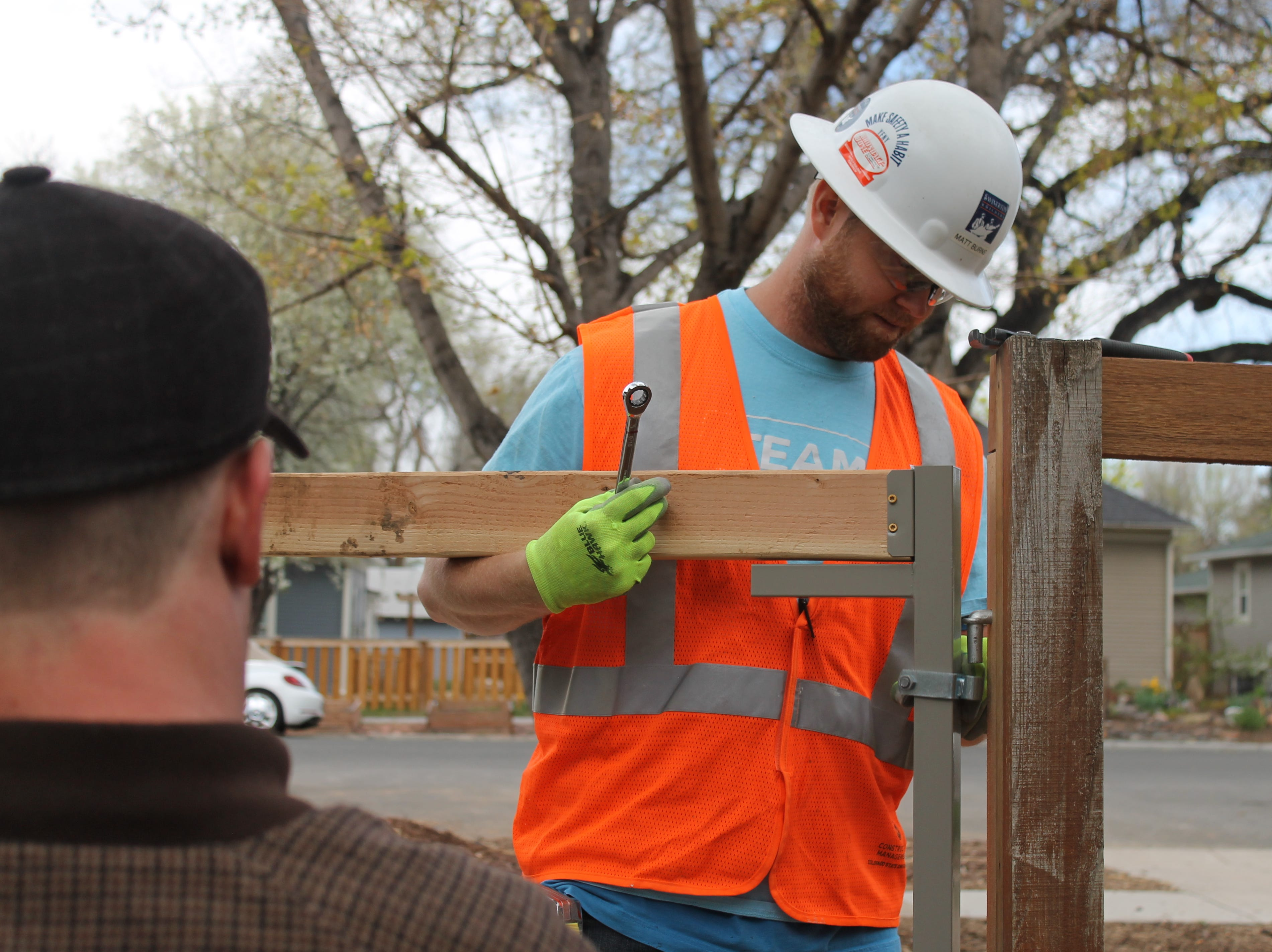 Matt Burns works to build a gate that will be easy for homeowner Terry Schlicting to use in his wheelchair. Schlicting, who is pictured chatting with Burns,  said throughout the project, students have treated him like a friend and a project manager -- not like a charity case. That's exactly how he likes it, he said.