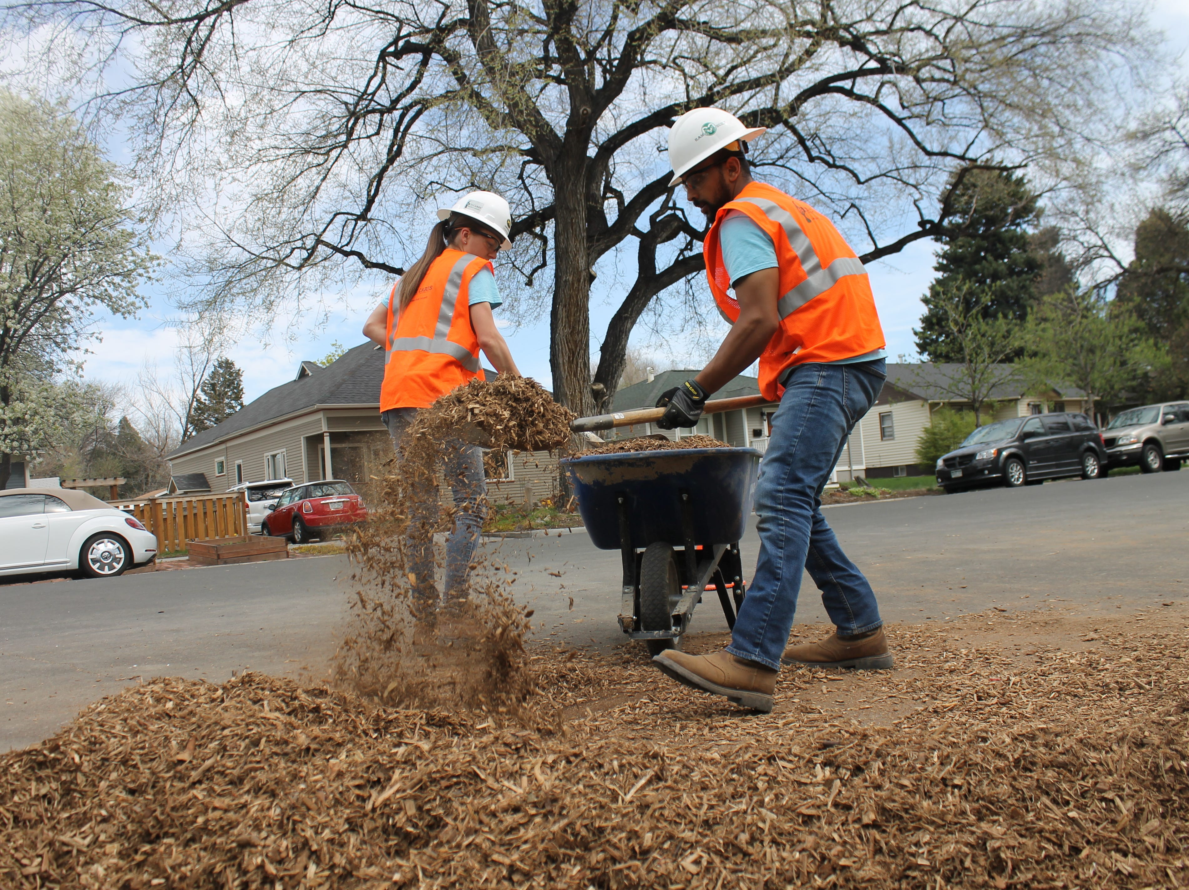 Leigha Huck, left, and Saleh Bawareth shovel mulch into a wheelbarrow Saturday, April 27, 2019. They're both construction management students at Colorado State University, working with Construction Management Cares for class. The program aims to make homes and nonprofits more accessible to folks with disabilities.