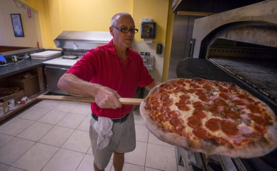 Joe Calderone, owner of Joe Daddy's Pizza in Cape Coral, readies a Neapolitan pizza pie for a customer, Friday afternoon, April 26, 2019.