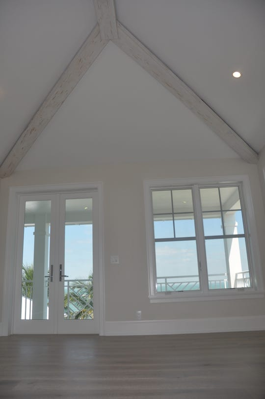 The upstairs master suite has high peaked ceilings with white washed wood beams and French doors that lead to the balcony.