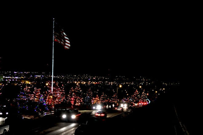 Christmas lights shine over Great Falls at Overlook Park after the reading of the names at the Memorial Christmas Tree Lighting Sunday.