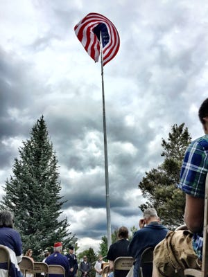 The flag at Overlook Park whips in the wind during the annual Great Falls Flag Day ceremony put on by the Great Falls Association of Realtors.