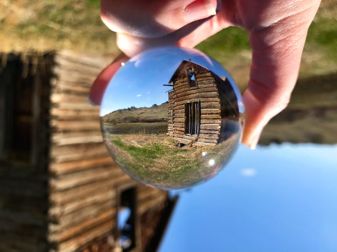A crystal ball reflects an old log building in the Bear Paw Mountains near Warrick