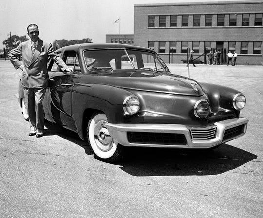 Preston Tucker poses in this 1947 photo next to a hand-built model of the car bearing his name.