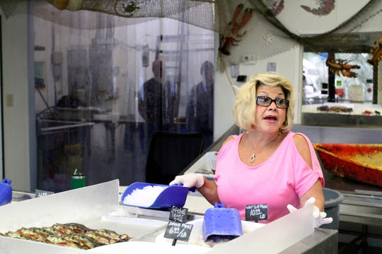 In this April 17, 2019 photograph, Angie Desporte and other employees at Desporte & Sons Seafood opened shop on Division Street in Biloxi, Miss., expecting a busy day as the Lenten season nears its end. Her son, Sean Desporte, is back in charge of the entire business under Chancery Court orders. Co-owner Artie Desporte and his wife Becky are not allowed on the property while a lawsuit over business control is pending.