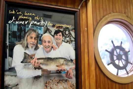 "In this April 17, 2019 photograph, a framed picture of the three generations of Desportes, from left, Artie, his father Emile ""Junior"" and Sean Desporte that depicts happier times, hangs in their Biloxi, Miss., seafood business. The family patriarch, Junior, did not live to see his son and grandson at odds over the five-generation Biloxi business."