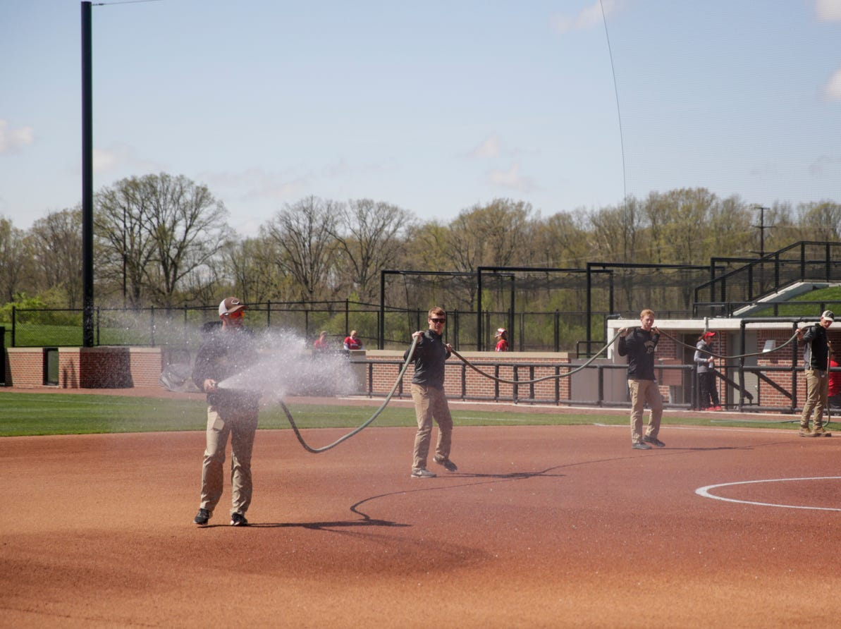 The Purdue grounds crew waters the infield before the first inning of a NCAA softball game, Sunday, April 28, 2019 at Bittinger Stadium in West Lafayette. Wisconsin won, 4-1.