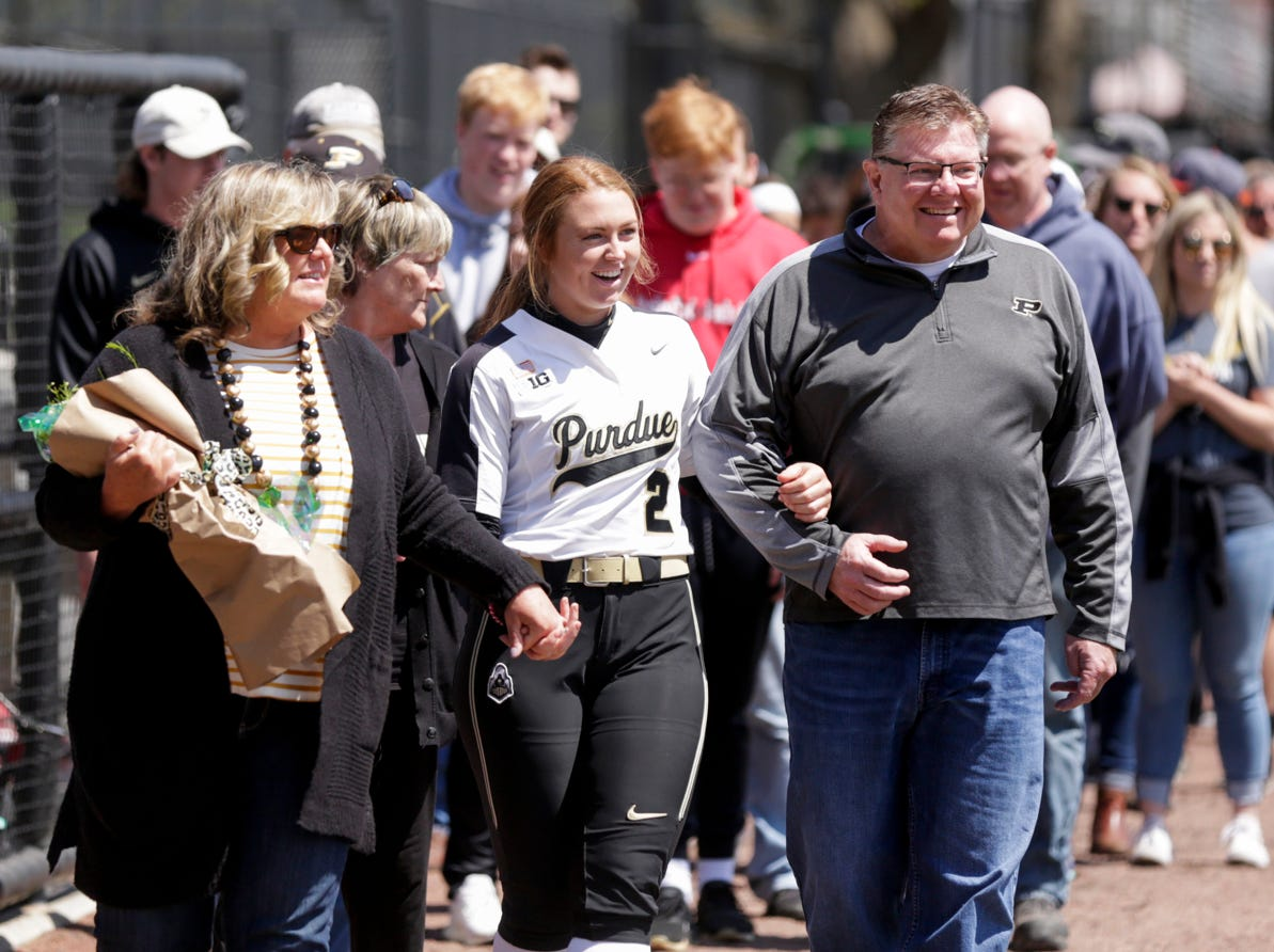 Purdue left fielder Mallory Baker (2) walks out with her parents during senior night ceremonies, Sunday, April 28, 2019 at Bittinger Stadium in West Lafayette.