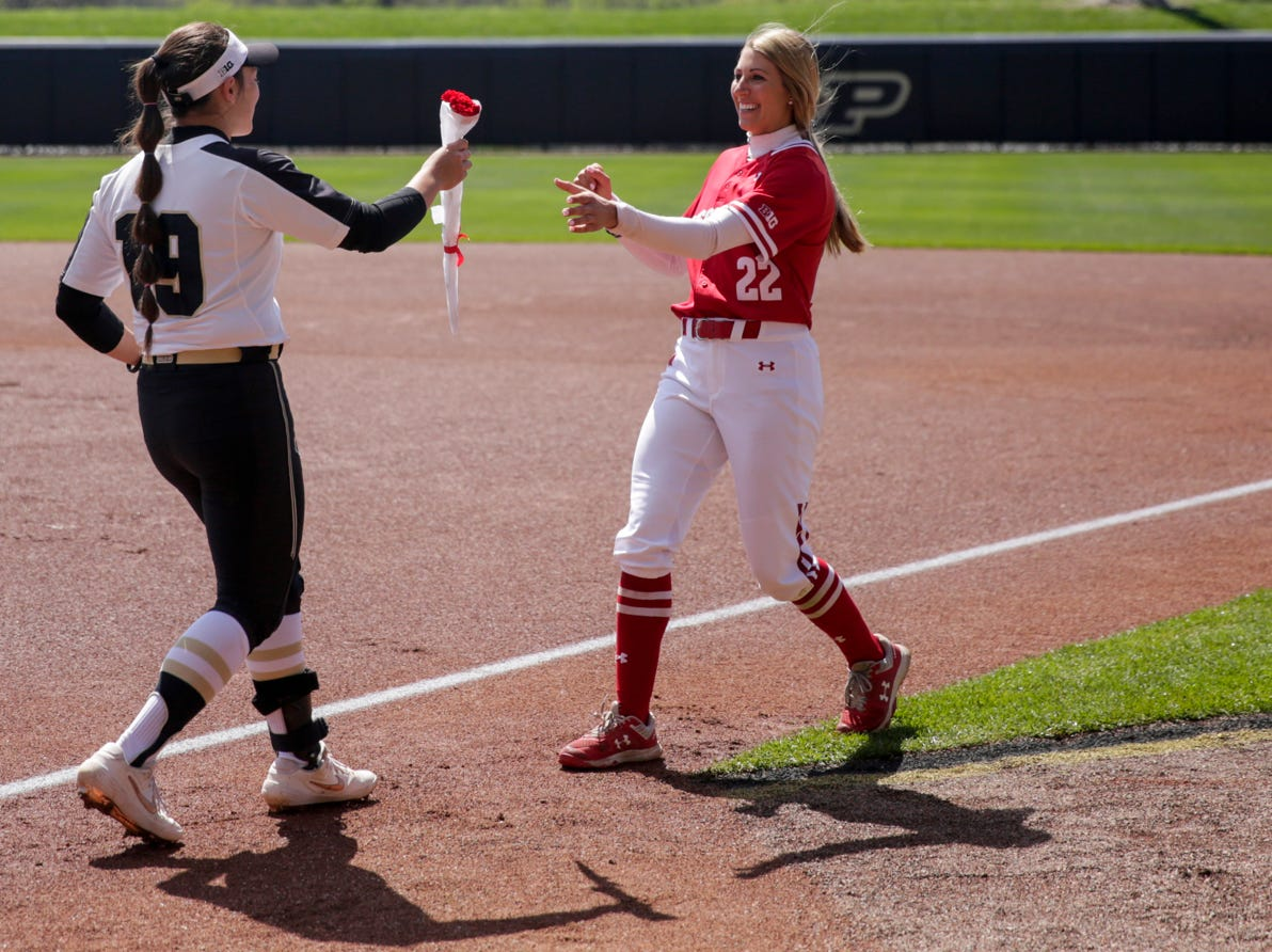 Purdue utility player Becca Jones (19) hands Wisconsin outfielder Gabby Scherle (22) a rose before the first inning of a NCAA softball game, Sunday, April 28, 2019 at Bittinger Stadium in West Lafayette. Wisconsin won, 4-1.