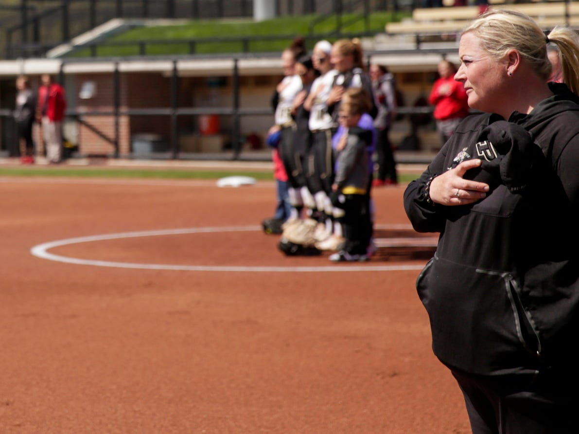 Purdue head coach Boo De Oliveira stands during the national anthem before the first inning of a NCAA softball game, Sunday, April 28, 2019 at Bittinger Stadium in West Lafayette. Wisconsin won, 4-1.