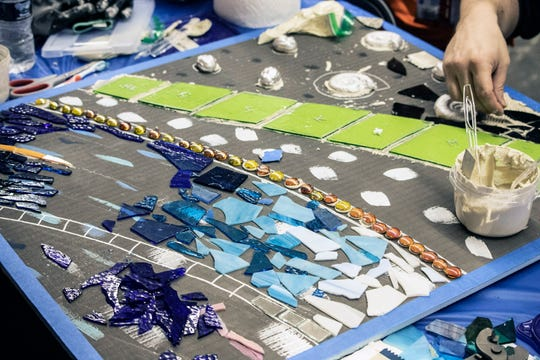 A variety of colorful and shiny raw materials are arranged into mosaic art by volunteers participating in a Saturday morning jam session in Jeffersonville, Indiana. 4/20/19