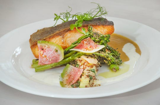 The Pine Room restaurant's Verlasso Salmon is made with coconut red curry, grilled broccolini, Yuzu creme fraiche, vegetable quinoa, charred scallion oil, garlic chips, seasoned watermelon radish and Happy Sprouts Farm pea shoots. April 24, 2019