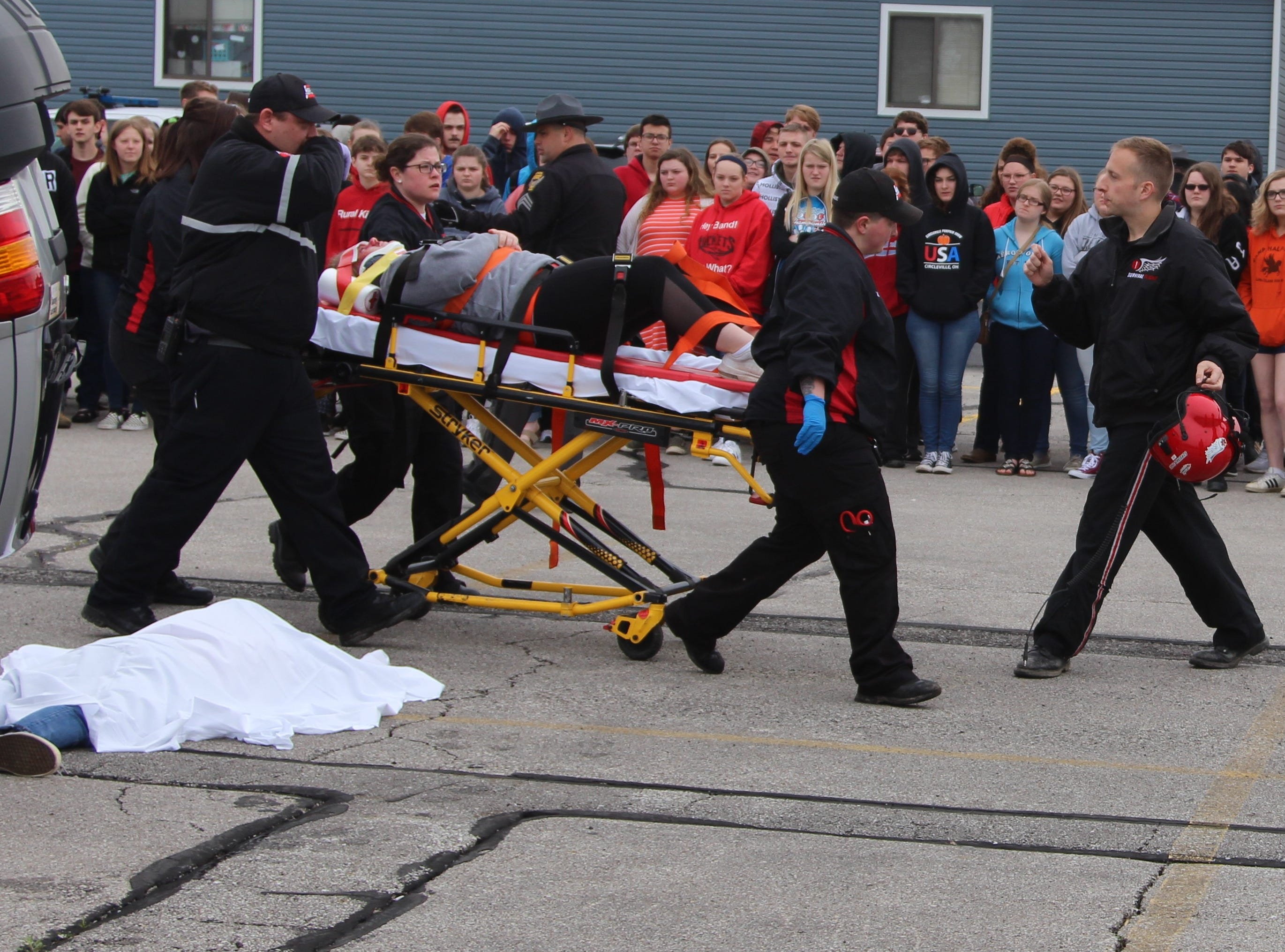 "Paramedics assist an ""injured"" motorist Monday morning during a mock crash held at Ridgedale Jr./Sr. High School. Principal Greg Rossman said it has been more than eight years since the school has hosted the scenario meant to show students the dangers of distracted and drunk driving."