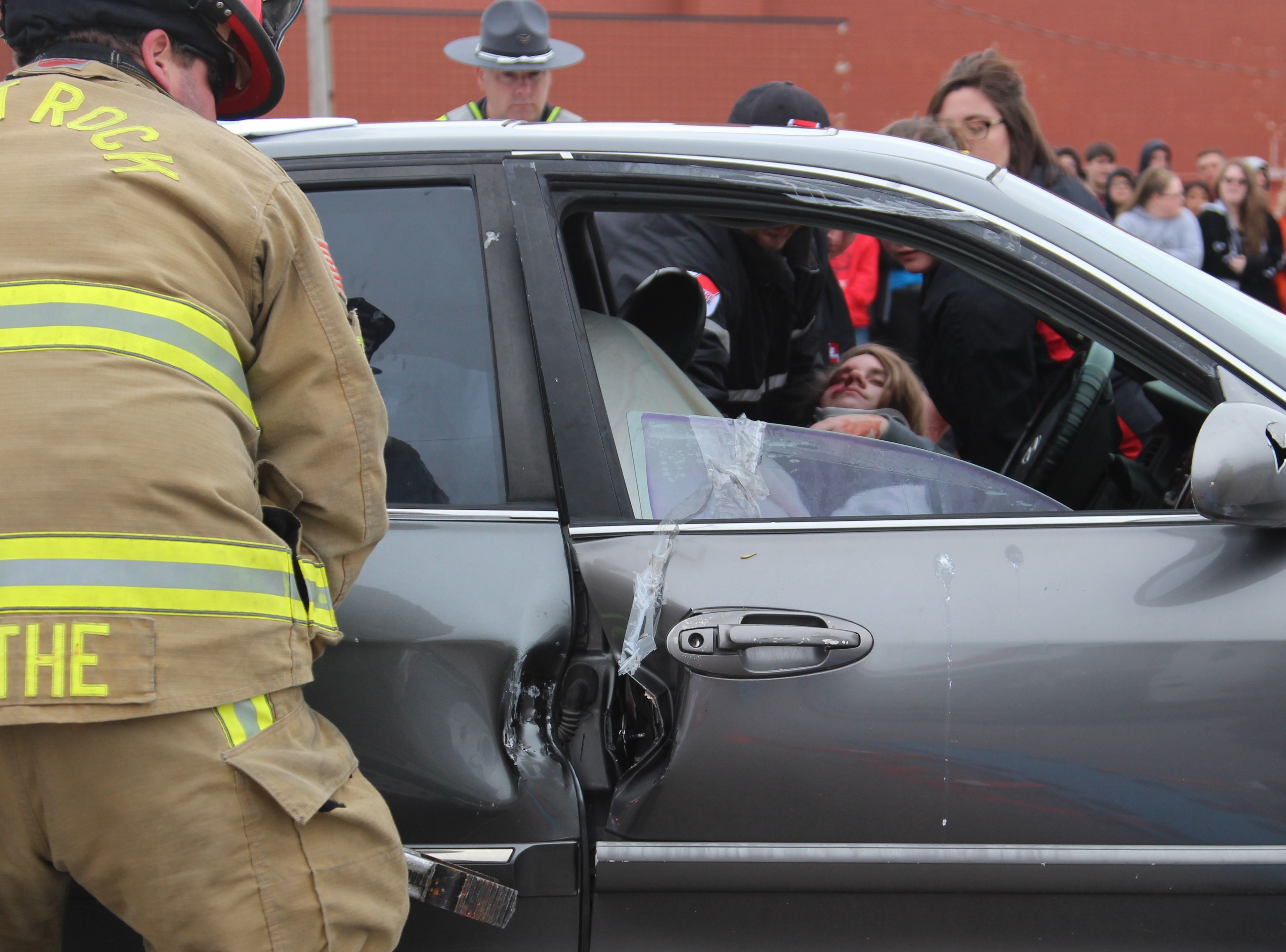 "Firefighters with the Salt Rock Fire Department assist an ""injured"" motorist Monday morning during a mock crash held at Ridgedale Jr./Sr. High School. Principal Greg Rossman said it has been more than eight years since the school has hosted the scenario meant to show students the dangers of distracted and drunk driving."
