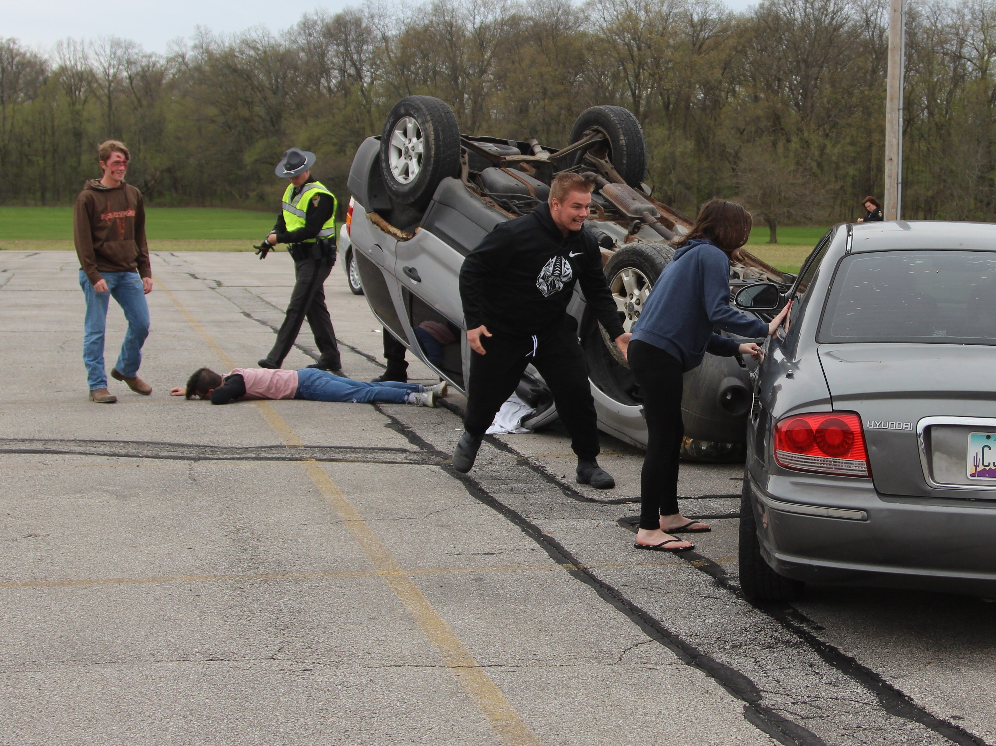 "Students run towards their ""injured"" peers during a mock crash at Ridgedale Jr./Sr. High School Monday morning."