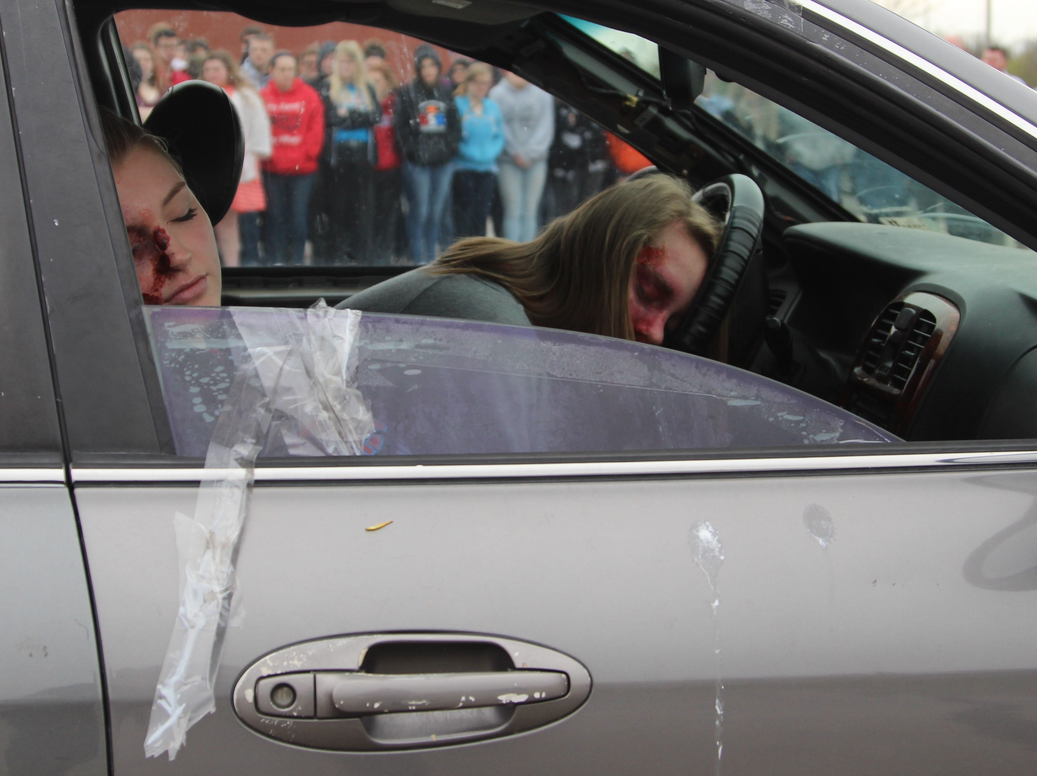 "Ridgedale High School students watch as two of their peers portray injured motorist during a mock crash Monday morning. The staged ""accident"" is meant to show the dangers of distracted and drunk driving.  The scenario took place in the north parking lot of the school in preparation for Ridgedale's prom night this Saturday."
