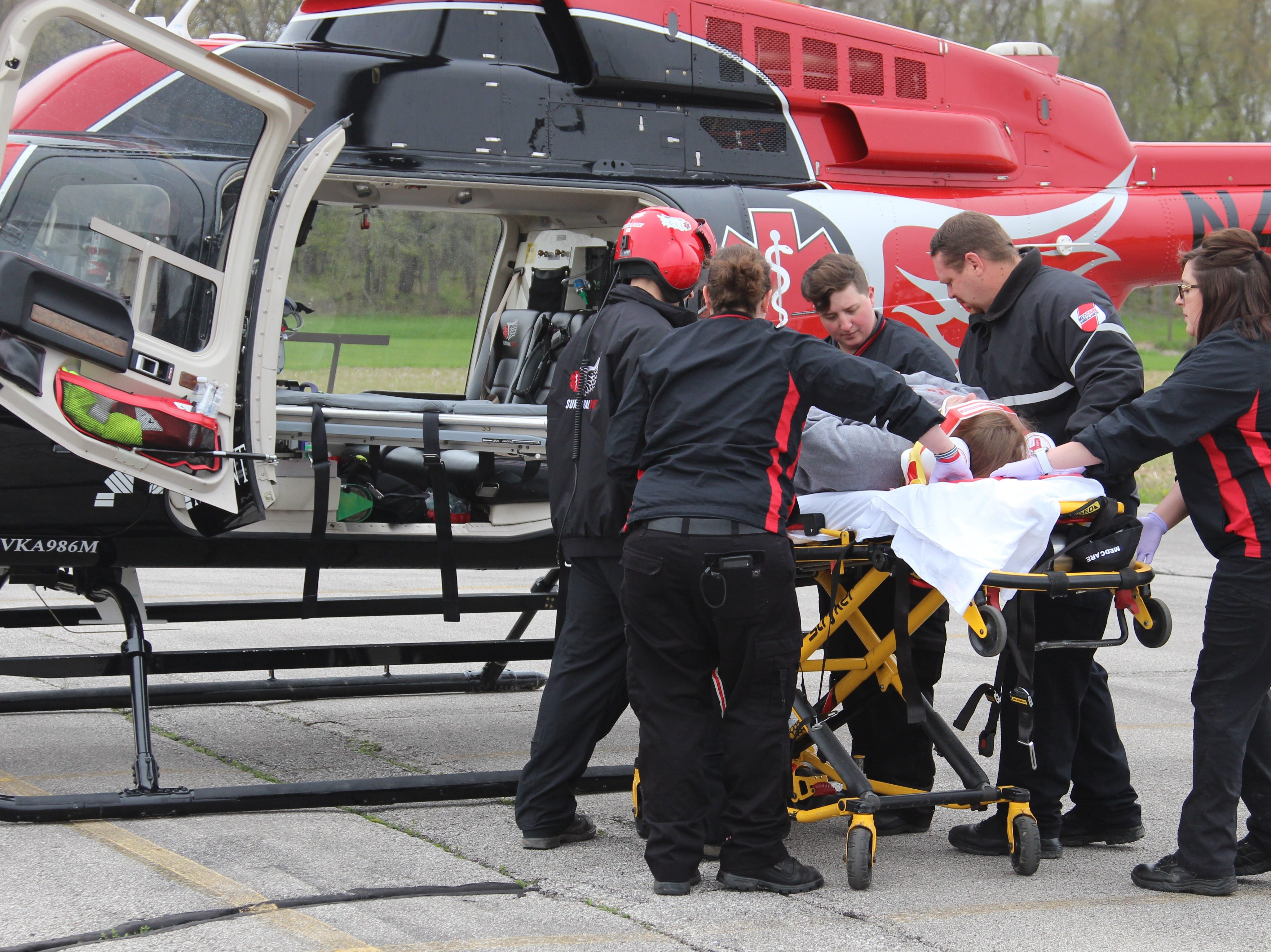 "Paramedics place an ""injured"" motorist into a helicopter during a mock crash at Ridgedale Jr./Sr. High School Monday morning.  Principal Greg Rossman said it has been more than eight years since the school has hosted the scenario meant to show students the dangers of distracted and drunk driving."