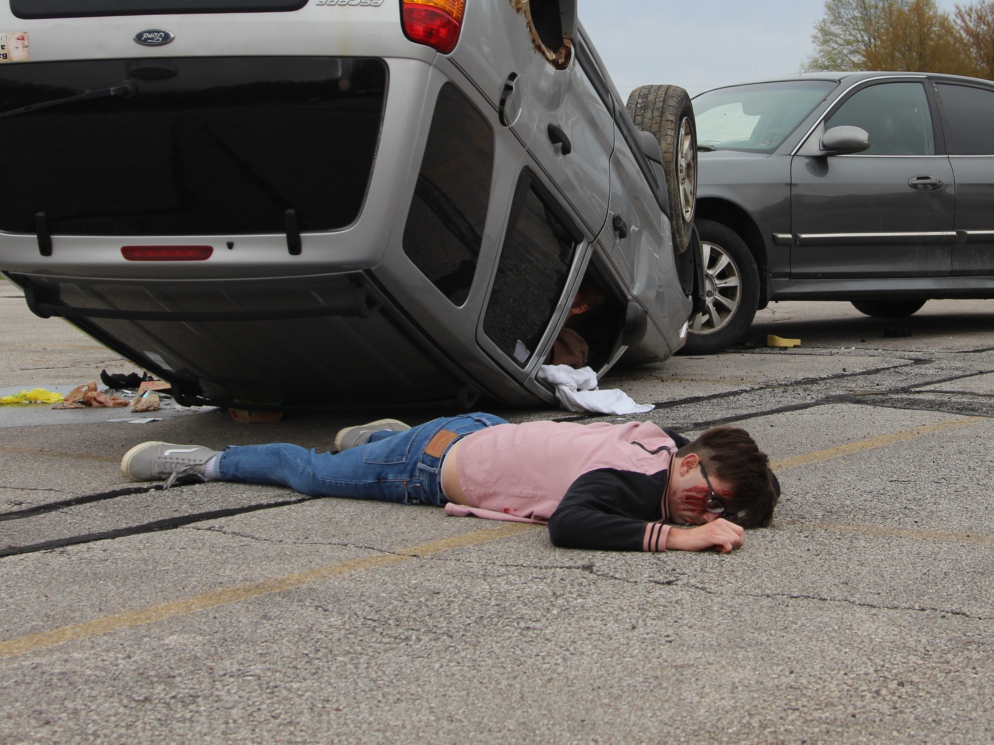 "Ridgedale High School students watch as one of their peers lays ""dead"" on the ground during a mock crash Monday morning. The staged ""accident"" is meant to show the dangers of distracted and drunk driving."
