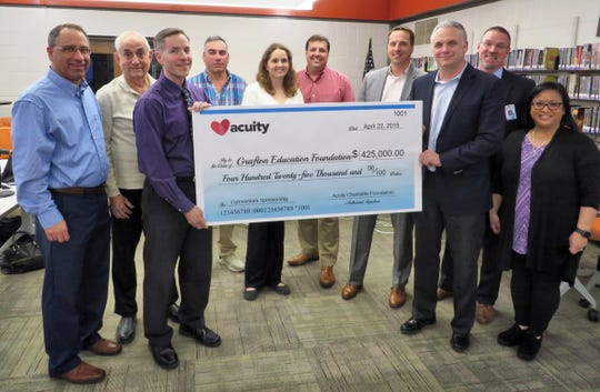 Acuity Insurance recently made a $425,000 donation to the Grafton School District, which in turn granted Acuity naming rights to Grafton High School's main gym. Pictured are (from left)  Grafton School Board Treasurer Mark Koehler, Grafton Education Foundation member Bob Hoffman, Acuity Charitable Foundation's Adam Norlander, Grafton School Board member John Scolman, Grafton School Board Vice President Carrie Walls, Grafton School Board member Steve Nauta, Grafton School Board member Jerry Rossi, Grafton School Board president Paul Lorge, Grafton Schools Superintendent Jeff Nelson and Grafton School Board Clerk Jo Maehl.