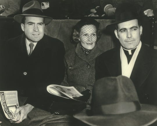 Father Theodore Hesburgh (right) takes in a Notre Dame-Southern California football game in 1952 with Vice President-elect Richard Nixon and his wife, Pat. (Hesburgh and Nixon were friends for years, but Nixon later fired the priest for chairing a civil rights commission that criticized Nixon's administration.) Hesburgh's life is the focus of a new documentary.