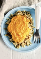 Philia Kelnhofer puts her secretly carrot cheese sauce over noodles for her two-year-old son, Ben.