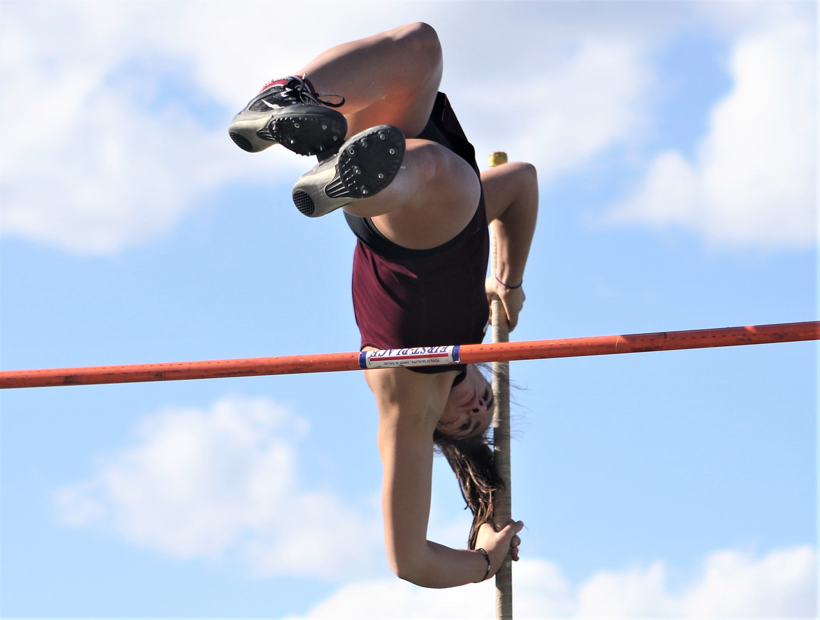 Skylar Kennedy of Menomonee Falls eyes the bar as she clears it during the pole vault competition at the Dan Benson Invitational at Wauwatosa West on April 26, 2019.
