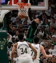 Celtics forward Daniel Theis dunks as Bucks forwards Giannis Antetokounmpo and Ersan Ilyasova watch Sunday.