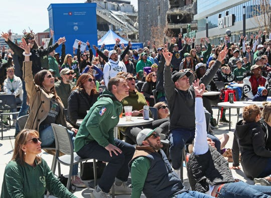 Fans in the plaza outside Fiserv Forum cheer for the Bucks during Sunday's game against the Celtics.