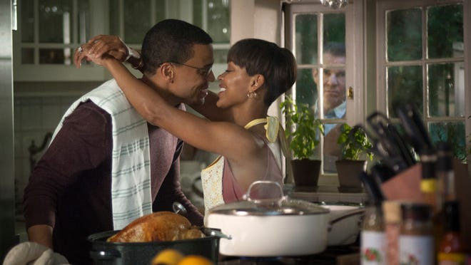 """Michael Ealy (left) and Meagan Good play a couple whose new house comes with an unwanted guest - the man (Dennis Quaid, in window in background) who lived there before and can't let go - in """"The Intruder."""""""