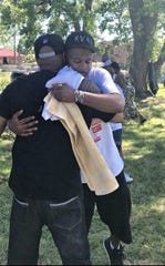 Jay Mayes embraces a friend after a Saturday shoot-out at Highland Villages Apartments that left one-injured. Mayes had helped the 9th annual community reunion the same day.