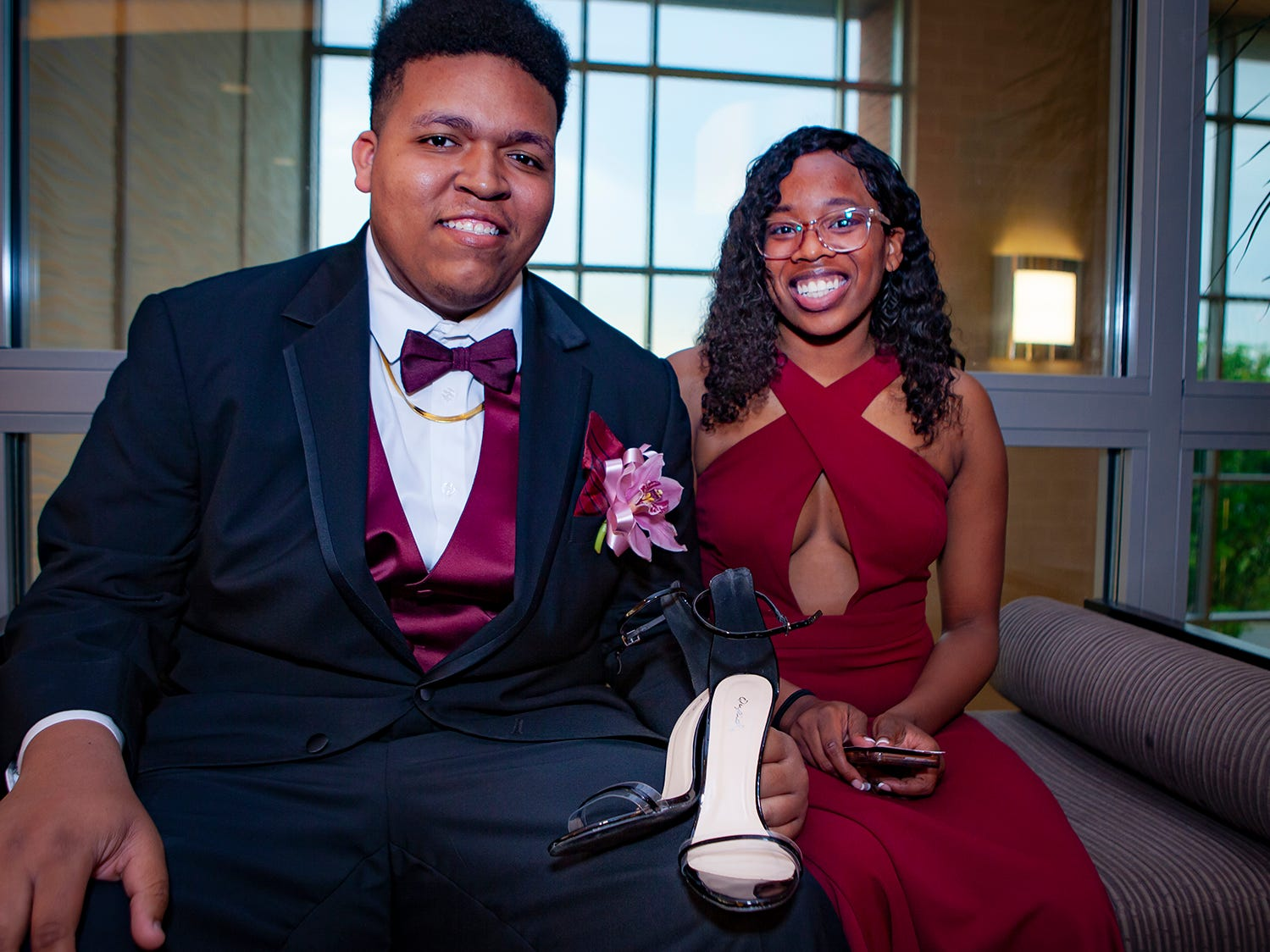 John Ragland holds date Dhasia Holliday's shoes at Riverdale's prom, held Saturday, April 27, 2019 at MTSU's Student Union Building.