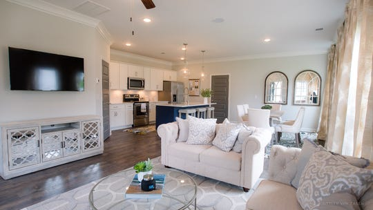The interior of Parkside Builders' model home at Waterford Village has an open floor plan, a kitchen island and hardwoods.