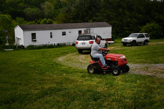Randall Barlow, a next door neighbor, mows the grass at the Cummins' house on Charles Brown Road Monday, April 29, 2019, in Westmoreland where six people were found dead the previous Saturday.